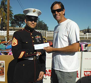 Staff Sergeant Colon accepts a check from WakeWorld's David Williams